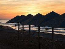 Die Regenschirme auf dem Ozean während des Sonnenuntergangs Lizenzfreie Stockbilder