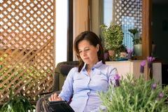 Die reife Frau, die das Internet grast und entspannen sich auf der Terrasse Lizenzfreie Stockfotos