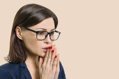 Die reife Frau mit Gläsern faltete ihre Arme betend meditiert, beige Hintergrund der Nahaufnahme, Kopienraum lizenzfreie stockfotos