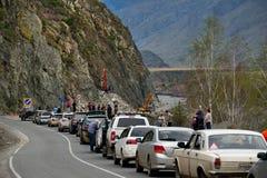 Die Reihe von Touristen auf Autos wartet auf den Abbau der schweren Straßenausrüstung des Steinschutts auf der Chui-Fläche in ein Stockfoto