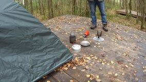 Die Reisendstellung nahe dem Zelt basiert auf und kochendem Wasser des Bretterbodens im Freien in einem Becher Er macht Tee Gesic stock footage