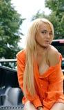 Die reizvolle junge Frau, die ein sitzt, unterstützen von aufheben Stockfotografie