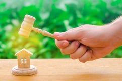 Die Richter ` s Hand hält einen Hammer nahe bei dem Holzhaus Versuch von Immobilien Beseitigung und Entfremdung des Konkurses, Co lizenzfreies stockbild