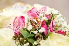 Die Ringe auf den Blumen, in einem Kasten, auf einem weißen Gewebe auf Spielwaren, Farben, Heiratsdetails, Eheringe Lizenzfreie Stockfotos