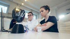 Die Roboterhand bewegt sich, den Bewegungen des behinderten Mädchen ` s Armes im Labor folgend stock video footage