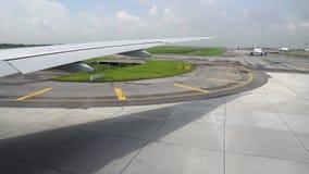 Die Rollbahn unter Flügel von Flugzeugen Flugzeug, welches die Rollbahn im Anschluss der Abfahrt im Flughafen weitergeht stock video