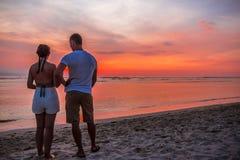 Die romantischen Paare, die auf einem Strand stehen, schließen thogether in den Sonnen lizenzfreie stockfotos