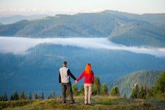 Die romantischen Paare, die einen Morgen genießen, schikanieren über den Bergen Stockfoto