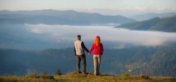 Die romantischen Paare, die einen Morgen genießen, schikanieren über den Bergen Stockbilder