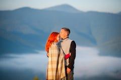 Die romantischen Paare, die einen Morgen genießen, schikanieren über den Bergen Stockfotografie