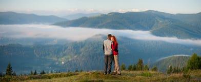 Die romantischen Paare, die einen Morgen genießen, schikanieren über den Bergen Stockfotos