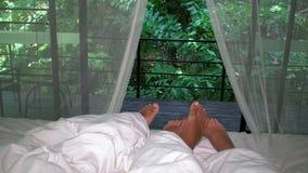 Die romantischen Paare, die im Bett mit weißen Vorhängen und Füßen in Richtung zum Fenster schlafen, öffnen sich zum wilden üppig stock video