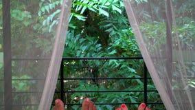 Die romantischen Paare, die im Bett mit weißen Vorhängen und Füßen in Richtung zum Fenster schlafen, öffnen sich zum wilden üppig stock footage