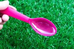 Die rosa Farbe des Löffels in der Mannhand Lizenzfreies Stockfoto