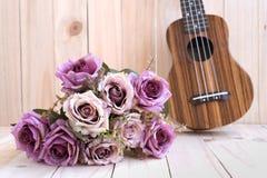 Die Rosen mit Ukulele auf hölzernem Hintergrund Stockbild