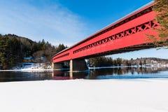 Die rote überdachte Brücke auf dem gefrorenen Fluss stockfotografie