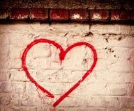 Die rote Liebes-Herzhand, die auf Backsteinmauerschmutz gezeichnet wurde, maserte Hintergrund Stockfotos