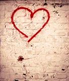 Die rote Liebes-Herzhand, die auf Backsteinmauerschmutz gezeichnet wurde, maserte Hintergrund Stockbild