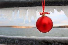 Die rote Weihnachtsverzierung, die an einem Eis hängt, bedeckte Schiene Stockfotos