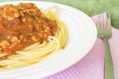 Die roten Soßenspaghettis in einem weißen Teller und in einem rosa Gewebe lizenzfreies stockfoto