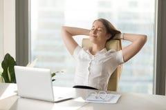 Die ruhige lächelnde Geschäftsfrau, die am bequemen Stuhl sich entspannt, übergibt b lizenzfreie stockfotos