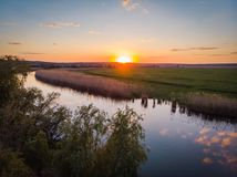 Die ruhige Oberfläche des Flusses, des orange Sonnenuntergangs, der Grünfelder und der Wiesen an einem ruhigen warmen Sommerabend Lizenzfreie Stockfotografie