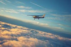Die runde Kurve der Erde abgedeckt durch goldene Wolken und ein sall einmotoriges Flugzeugfliegen im Sonnenuntergang lizenzfreie stockfotos