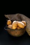 Die runden gelben Kartoffeln, die im Topf und auf dem Tisch die Beleuchtung liegen, ist zurückhaltendes rustikales Stockfoto