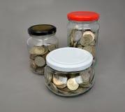 Die russische Metallwährung ist in den Glasgefäßen auf einem grauen backgro Stockfotos