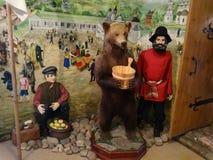 Die russischen Bauern der Ausstellung und der Bär Stockbild