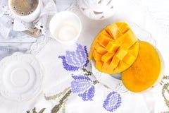 Die süße Mangofrucht wird in Würfel geschnitten Auf einer Spitzetischdecke und ein Tasse Kaffee und eine weiße Platte stockfotos