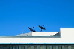 Die Satellitenschüssel auf dem Dachgebäude stockfoto