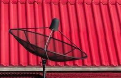 Die Satellitenschüssel lokalisiert hinter rosa Beschaffenheit Stockfotografie