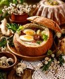Die saure Suppe, die vom Roggenmehl mit Wurst und Eiern gemacht wurde, diente in der Brotschüssel Traditionelle polnische saure R lizenzfreie stockfotografie