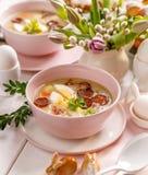 Die saure Suppe, die vom Roggenmehl mit Wurst und Eiern gemacht wurde, diente in der rosa keramischen Schüssel Traditionelle poln stockfotos