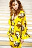 Die Schönheiten, die in einem stilvollen Sommer gelb mit braunem Blumenkleid gekleidet werden, geht in eine Stadtstraße an einem  lizenzfreie stockfotografie
