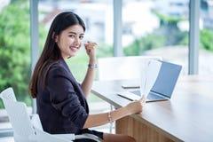 die schöne asiatische junge Geschäftsfrau hob Hände feiernd zum Erfolg an, der die Ziele und Hand halten Papierbelegdatei mit erz stockfoto