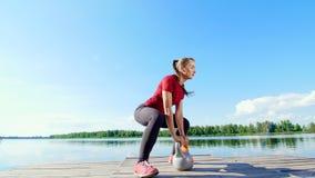 Die schöne, athletische junge blonde Frau, die verschiedene Übungen mit Gewichten, Dummköpfe, Laufleinen tut, hockt See, Fluss stock video