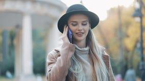 Die schöne attraktive Frau, die im Mantel und im Hut trägt, spricht telefonisch im Stadtzentrum auf einem sonnigen Frühlingswette stock footage