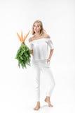 Die schöne blonde Frau, die frische Karotte mit Grün hält, verlässt auf weißem Hintergrund Gesundheit und Diät Stockfotografie