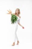 Die schöne blonde Frau, die frische Karotte mit Grün hält, verlässt auf weißem Hintergrund Gesundheit und Diät Lizenzfreie Stockfotografie