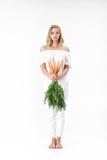 Die schöne blonde Frau, die frische Karotte mit Grün hält, verlässt auf weißem Hintergrund Gesundheit und Diät Stockbild