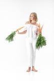 Die schöne blonde Frau, die frische Karotte mit Grün hält, verlässt auf weißem Hintergrund Gesundheit und Diät Lizenzfreie Stockfotos