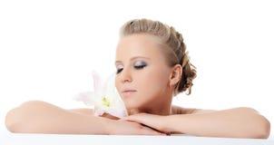 Die schöne blonde Frau mit Lilienblume Lizenzfreies Stockfoto