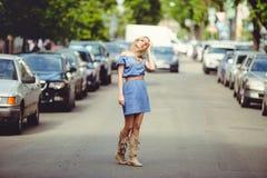 Die schöne blonde Frau, die in die Straße zwischen Autos geht, kleidete im blauen Kleid und in den Stiefeln an, bescheiden und wi Lizenzfreies Stockbild
