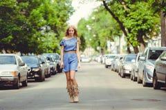 Die schöne blonde Frau, die in die Straße zwischen Autos geht, kleidete im blauen Kleid und in den Stiefeln an, bescheiden und wi Lizenzfreie Stockbilder