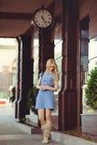 Die schöne blonde Frau, die unter dem Haus mit einer großen Uhr steht, kleidete in einem blauen Kleid und in den Stiefeln an, bes Stockfoto