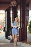 Die schöne blonde Frau, die unter dem Haus mit einer großen Uhr steht, kleidete in einem blauen Kleid und in den Stiefeln an, bes Lizenzfreies Stockfoto