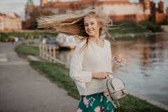 Die schöne blonde junge Frau, die neben dem Fluss bei Sonnenuntergang geht, haben Spaßlächeln und -spiel auf Kamera Stockfotos