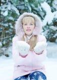 Die schöne blonde junge Frau, die rosa Jacke mit einer Haube trägt, hält Schnee auf ihren Händen Stockfoto